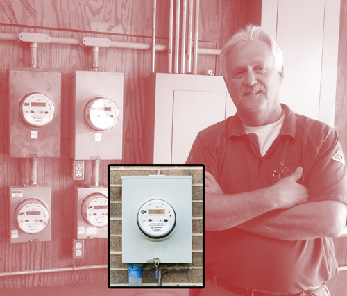 Senior Meterman Preston Glover stands in front of some of Conway Corp.'s smart meters. Courtesy Conway Corp