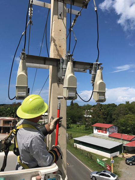 Lineman working to enable pole-top communication on a TripSaver® II Cutout Mounted Recloser. (photo courtesy of S&C Electric